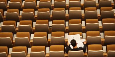 Man reading alone in an auditorium