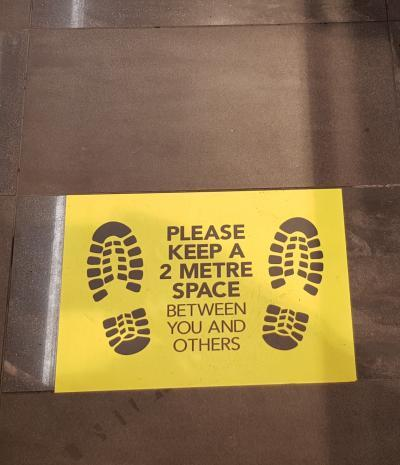 "Sign on the floor: ""Please keep 2 metre space between you and others"""