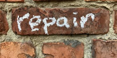 "Word ""repair"" written with chalk on a wall."